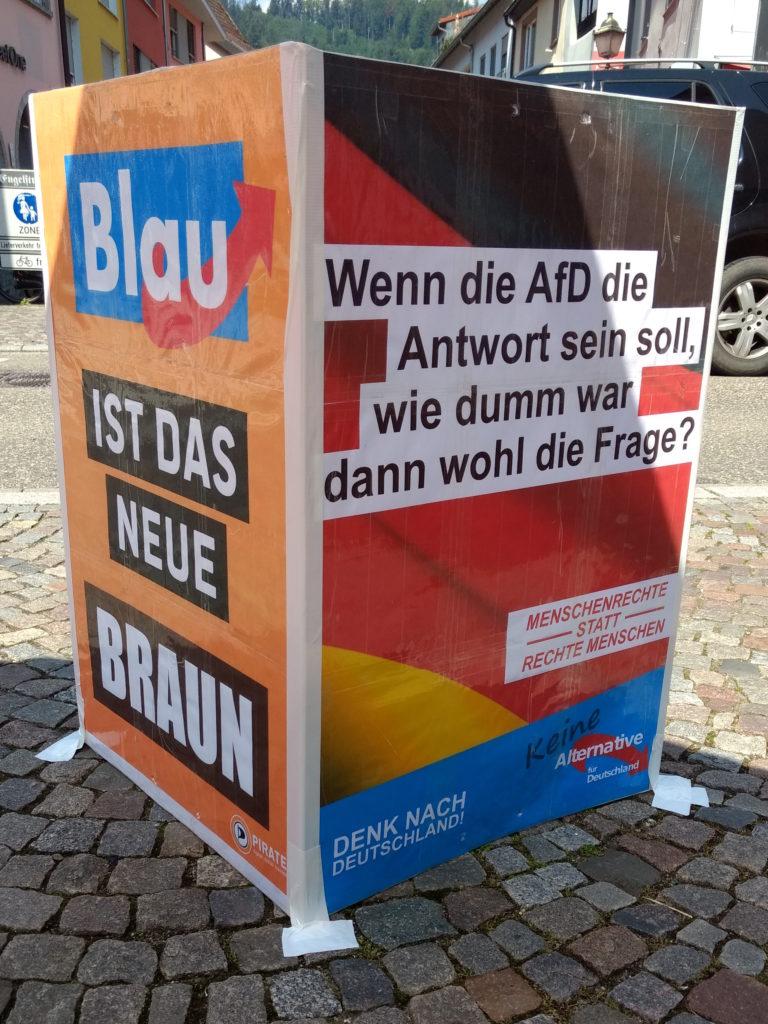 """Zwei Plakete mit den Aufschriften: """"Blau ist das neue Braun"""" und """"Wenn die AfD die Antwort sein soll, wie dumm war dann wohl die Frage?; Menschenrechte statt rechte Menschen; Keine Alternative für Deutschland""""."""