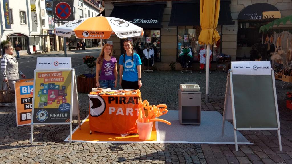 """Infostand, der durch einen orangefarbenen (links) und einen grauen Teppich (rechts) in zwei Hälften unterteilt ist. Links befinden sich ein Tisch mit Piratenflagge geschmückt, Infomaterial, Werbeartikel, ein Sonnenschirm im Piraten-Look, ein Eimer mit Ballonsäbeln und einem Kundenstopper mit einem """"#SaveYourInternet""""-Plakat und der Aufschrift """"Europa mit Piraten"""". Hinter dem Tisch stehen Annette Linder und Julia Fiedler. Rechts steht ein kleines graues Schränkchen mit einem alten Faxgerät darauf und ein Kundenstopper ohne Inhalt (graue Fläche) und der Aufschrift """"Europa ohne Piraten""""."""
