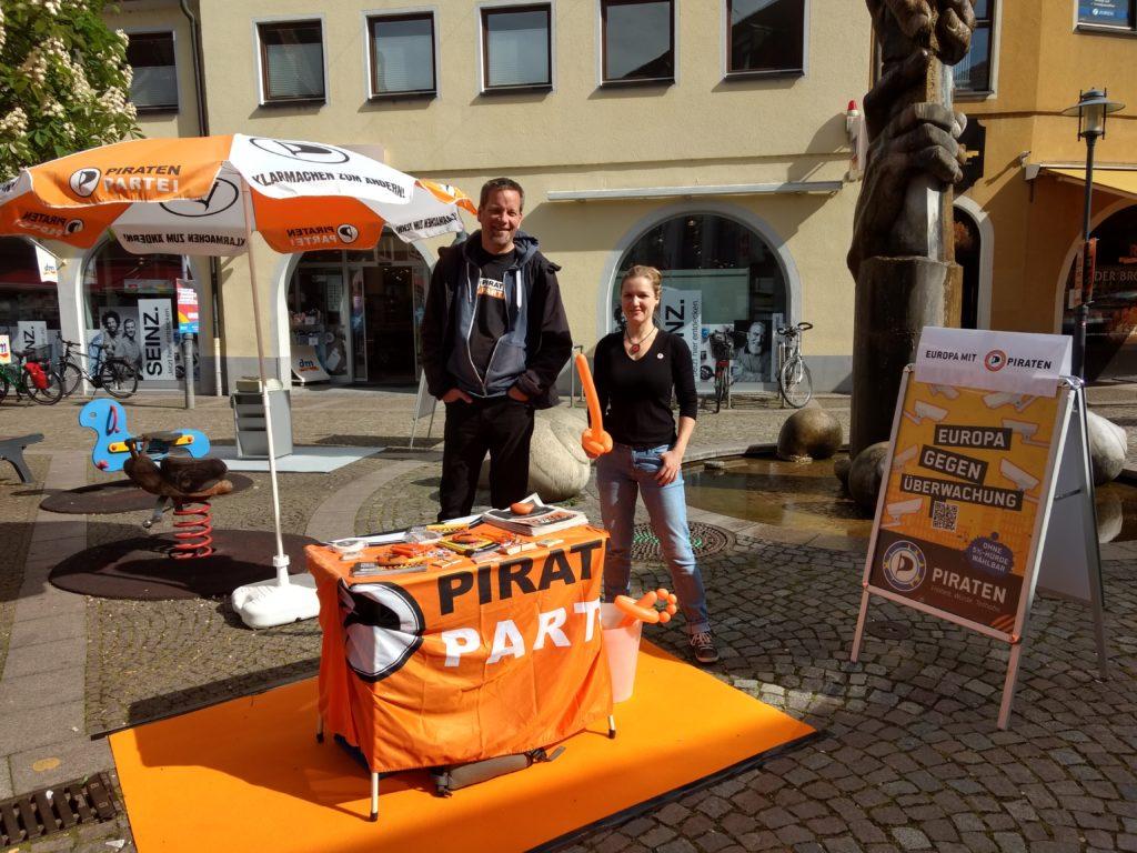 """Tisch, geschmückt mit einer Piratenflagge, Infomaterial und Werbeartikeln auf einem orangefarbenen Teppich. Daneben stehen ein Sonnenschirm im Piraten-Look und ein Kundenstopper mit einem """"Europa gegen Überwachung""""-Plakat und der Aufschrift """"Europa mit Piraten"""", dahinter André Martens und die mit einem Ballonsäbel """"bewaffnete"""" Annette Linder."""
