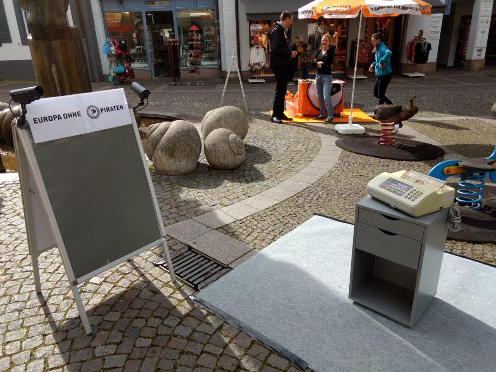 """Ein Kundenstopper ohne Inhalt (graue Fläche) und der Aufschrift """"Europa ohne Piraten"""" neben einem grauen Teppich, aug dem ein kleines graues Schränkchen mit einem alten Faxgerät steht."""