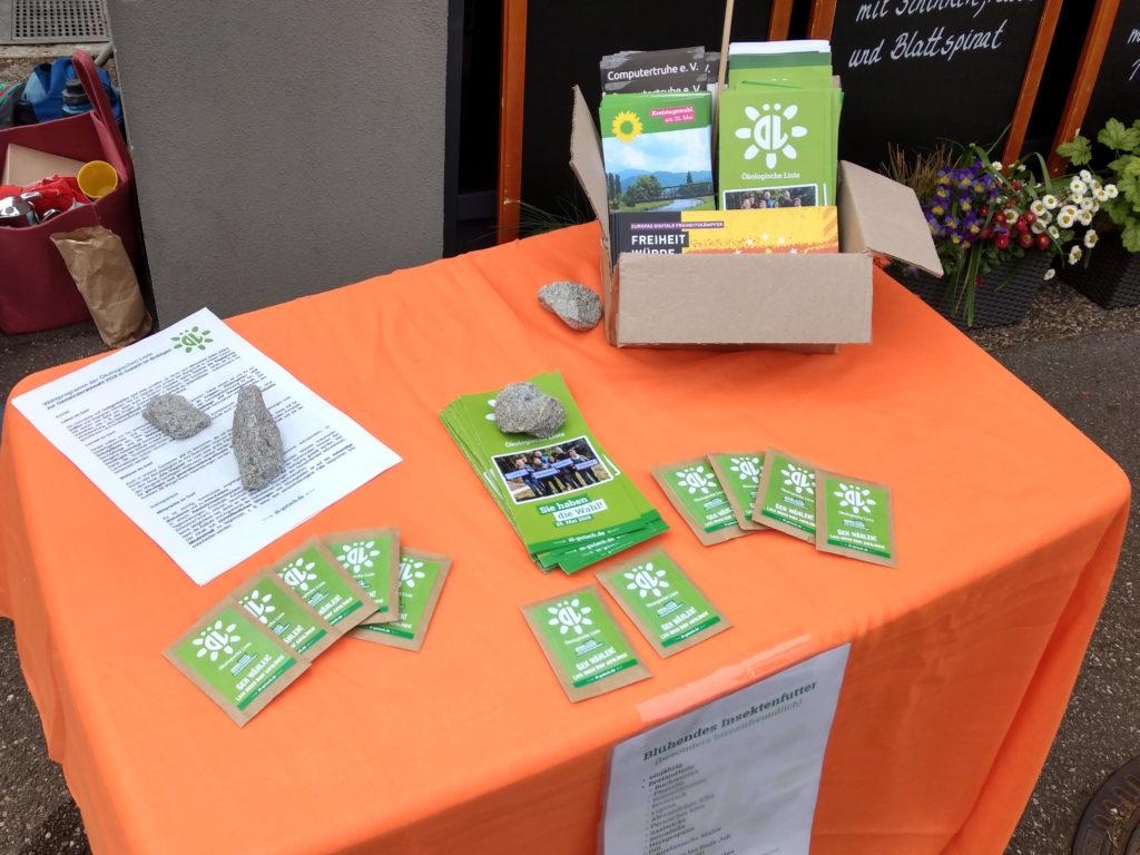 Tisch mit orange-farbener Decke, auf dem sich durch Steine beschwerte ÖL-Flyer und ÖL-Wahlprogramme, mehrere Saatguttütchen und eine Schachtel mit Infomaterial der Piraten, der Grünen und der Computertruhe befinden.