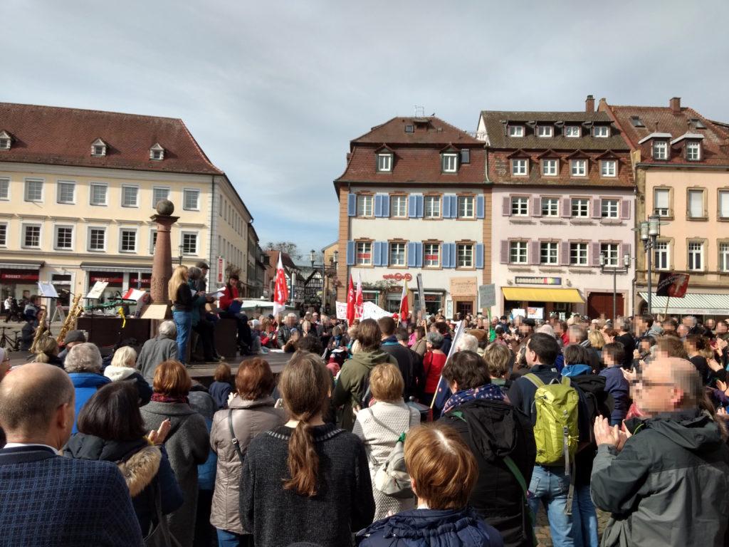 Blick auf den Emmendinger Marktplatz, der voller Menschen ist, von denen einige Transparente oder Flaggen in die Höhe halten. Auf dem Brunnen stehen die Initiator*innen der Veranstaltung.