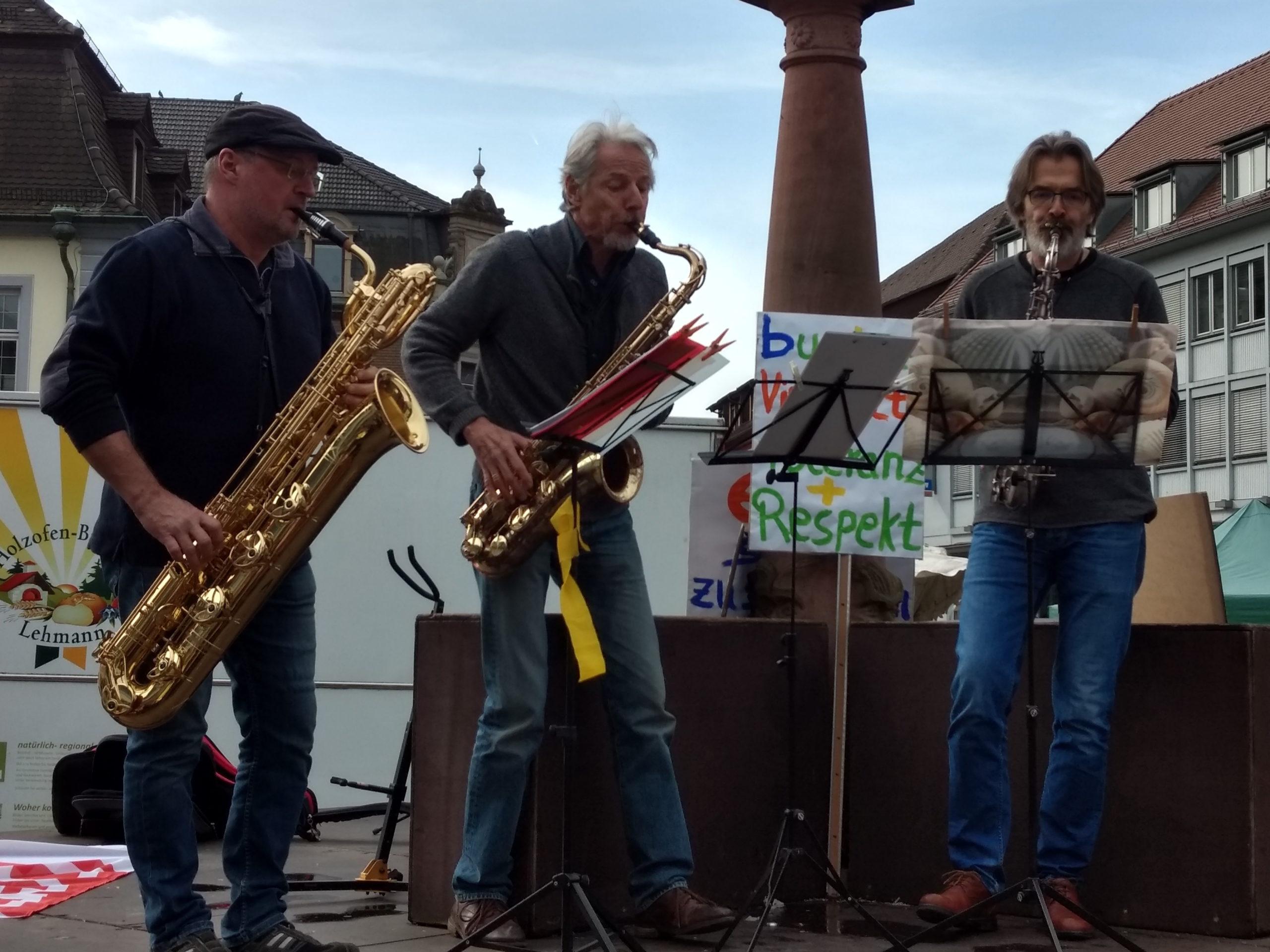 Drei Saxophon spielende Männer auf dem Brunnen des Emmendinger Marktplatzes.