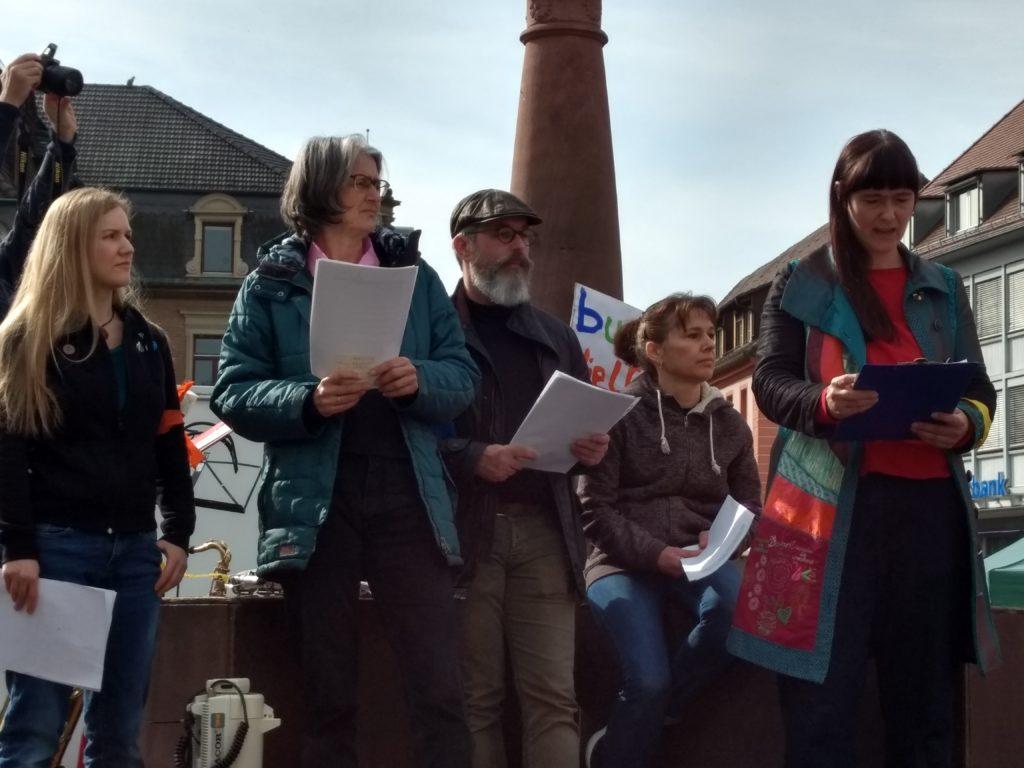 Vier Frauen und ein Mann stehen mit Zetteln in der Hand auf dem Marktplatzbrunnen, während eine der Frauen gerade ein Statement verliest.