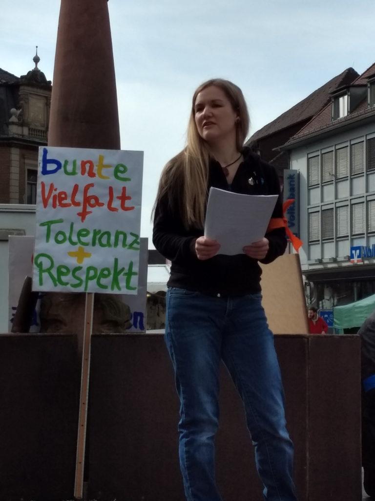 """Annette Linder auf dem Marktplatzbrunnen beim Vortragen eines Statements, welches sie von einem Zettel abliest. Hinter ihr steht ein Transparent mit der Aufschrift """"bunte Vielfalt + Toleranz + Respekt""""."""