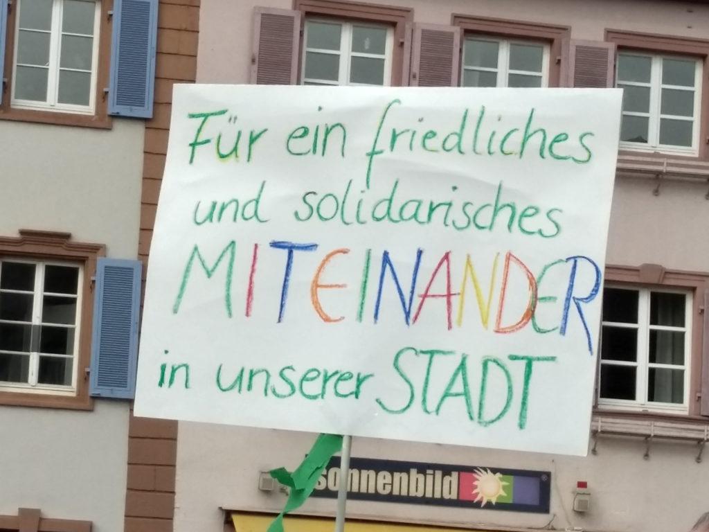 """Transparent mit der Aufschrift """"Für ein friedliches und solidarisches MITEINANDER in unserer STADT""""."""