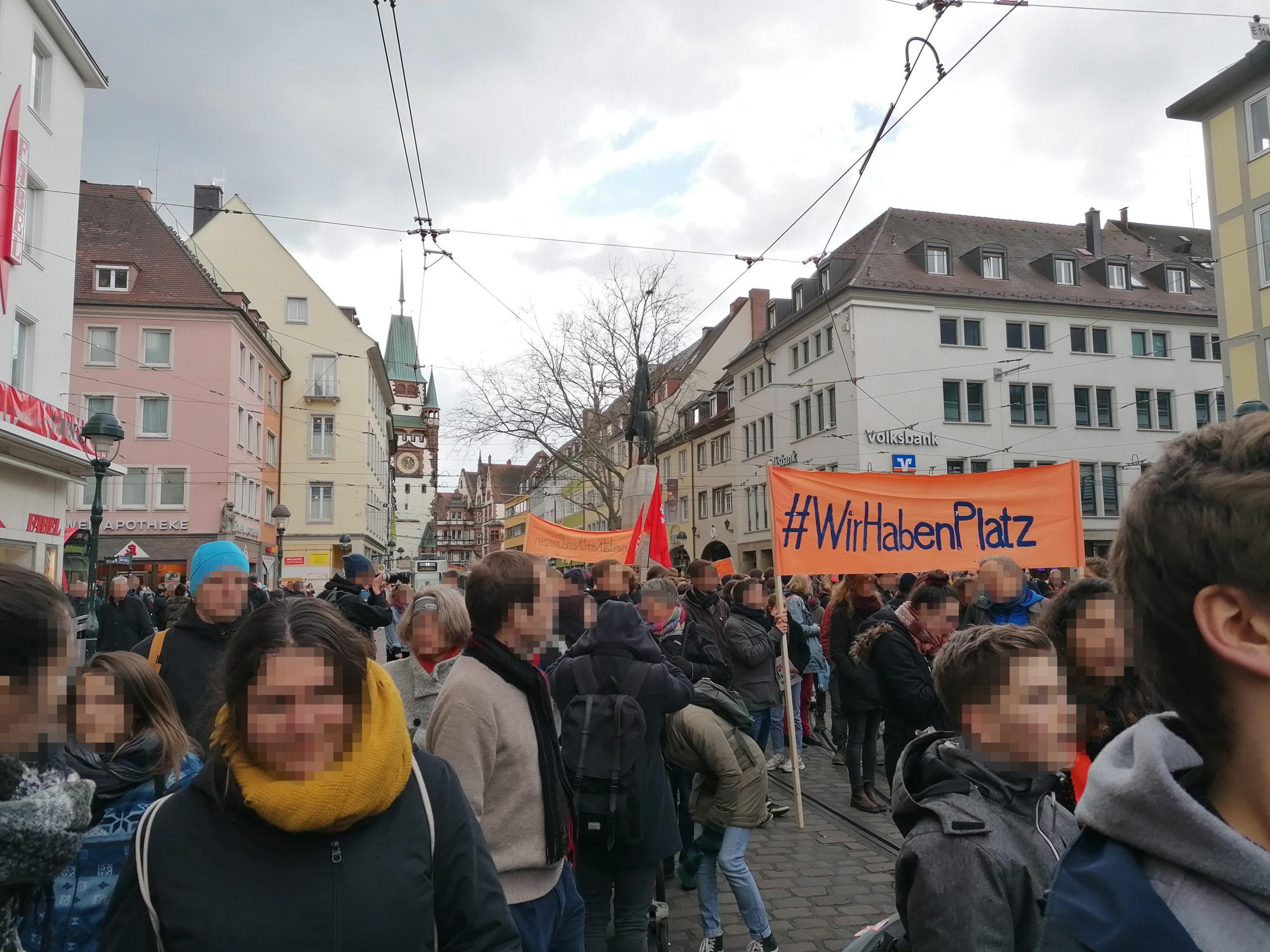 """Viele Menschen befinden sich während des Demozugs am Bertholdsbrunnen. Auf einem Transparent ist zu lesen: """"#WirHabenPlatz"""""""