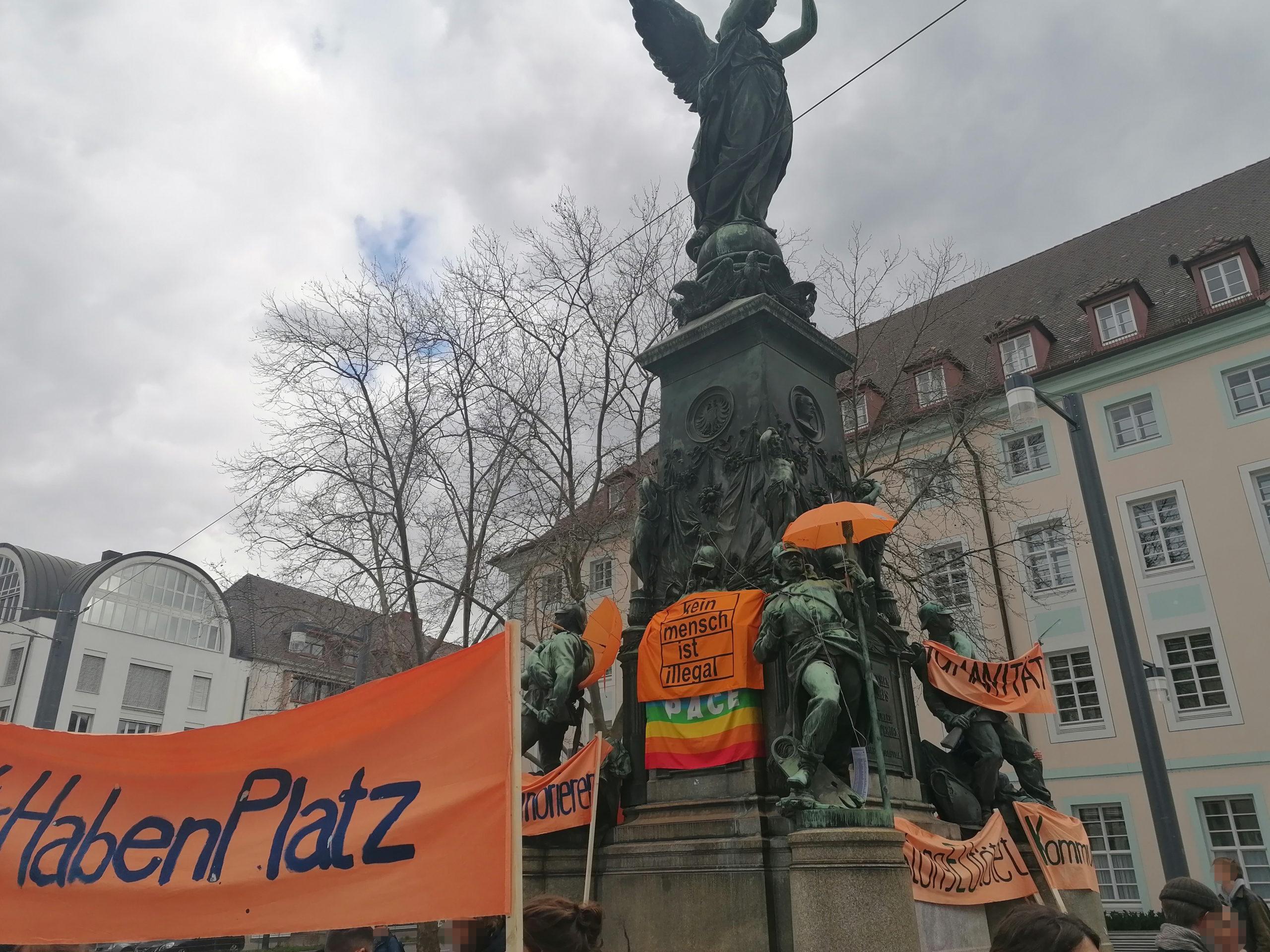"""Das Siegesdenkmal auf dem Europaplatz ist mit orangefarbenen Transparenten und Regenschirmen bestückt. Auf einigen Transparenten kann man """"kein mensch ist illegal"""" oder """"Humanität"""" lesen."""